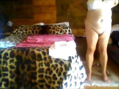 Chubby lies naked and then gets up to get dressed on her cam tube porn video