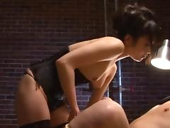 Gorgeous Asian in a tight black corset dominates a guy tube porn video