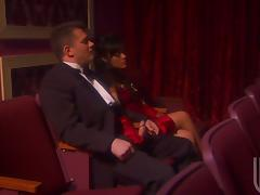 Brunette hottie Kaylani Lei gives a handjob to some man in a theatre tube porn video